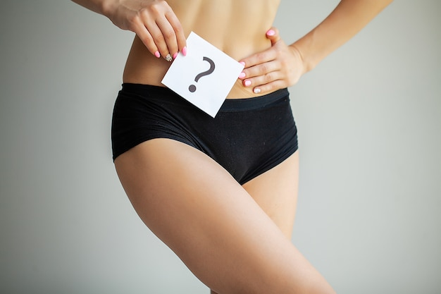 Health. woman body in underwear with question card near belly.