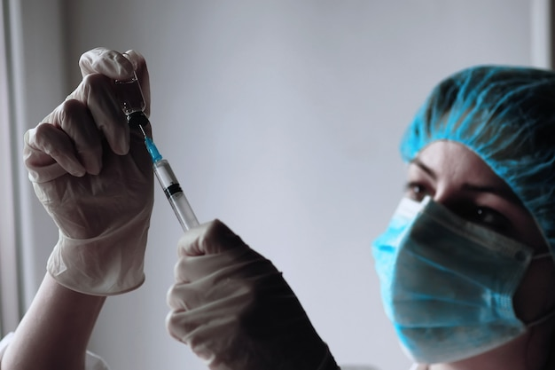 Health worker dials the vaccine into a syringe