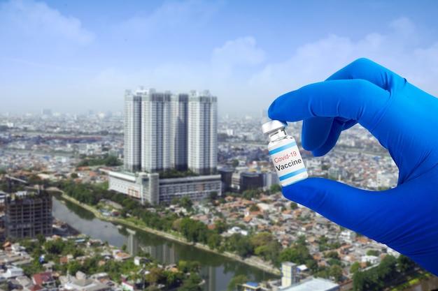 Рука медицинского работника с перчатками, держащая вакцины covid 19 для вакцинации в городе
