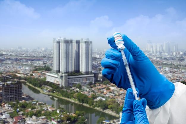Рука медицинского работника с перчатками, держащая шприц и вакцины covid 19 для вакцинации в городе