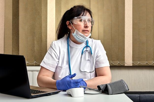 의료진은 코로나 바이러스 감염 코로나 19 전염병 기간 동안 환자를받는 사이에 사무실에서 쉬고 있습니다.