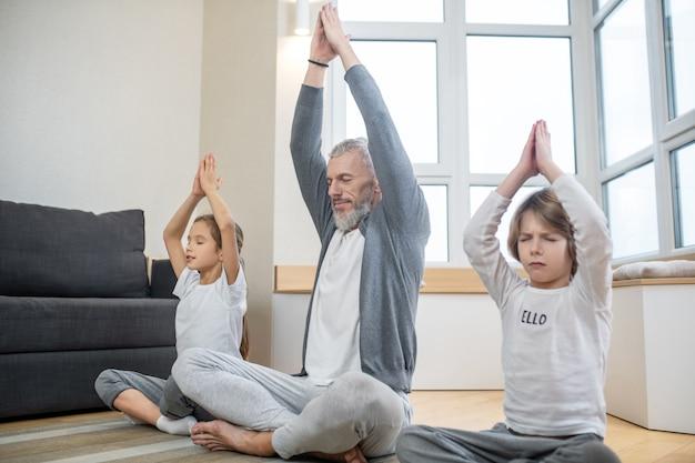 건강, 요가. 흰머리 성인 남자와 취학 연령의 두 자녀가 집에서 요가 자세로 앉아 눈을 감고 팔을 들고 침착하다