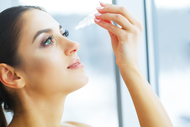 Health. young woman apply eye drops. fresh view. portrait of a beautiful woman with green eyes