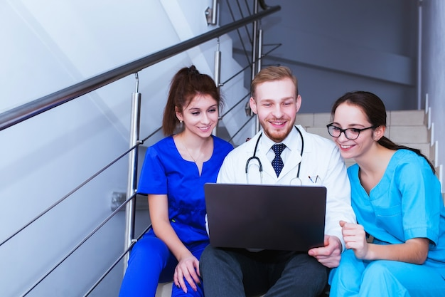 보건 의료. 의대생 그룹이 노트북 앞에서 의사소통을 하고 있습니다. 진단에 대한 토론.