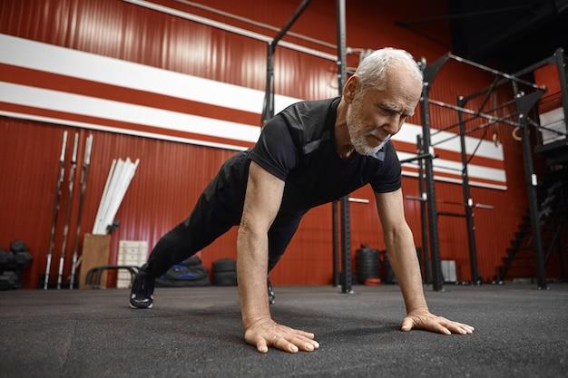 건강 관리, 나이, 은퇴 및 재활 개념. 체육관에서 판자를하고 운동복에 근육질 맞는 70 세 형태가 이루어지지 않은 남자. 피트 니스 센터에서 아침 운동 중 수석 남성 깔기