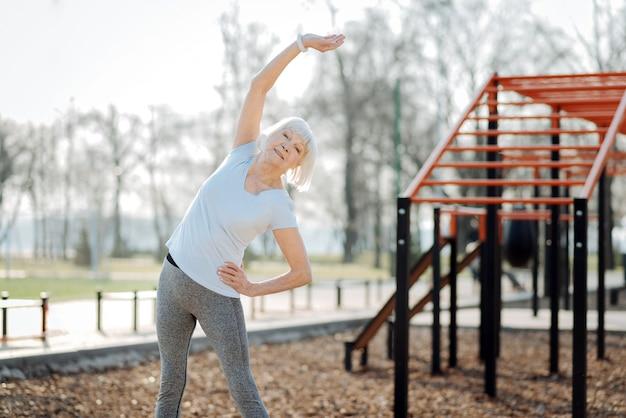 健康管理。スポーツ服を着て野外で運動している年配の女性に警告