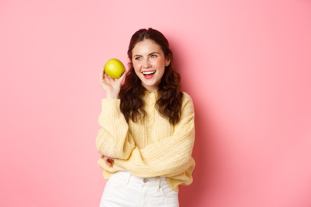 Концепция здравоохранения и образа жизни. веселая улыбающаяся женщина, демонстрирующая свою белую идеальную улыбку и зеленое яблоко возле лица, ест здоровые фрукты, стоит у розовой стены
