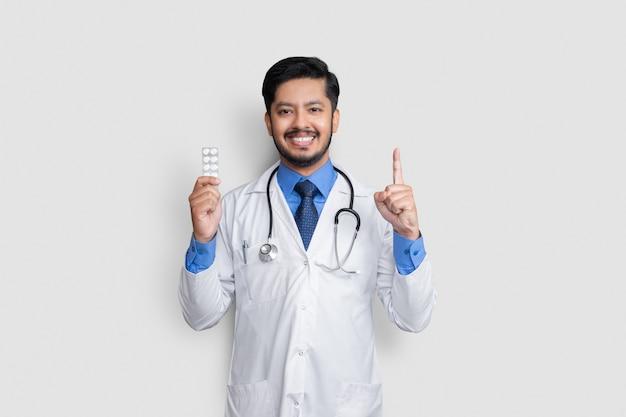 コピースペースのある白い壁に隔離された手にピルを持つヘルスケアと医療の概念の医師