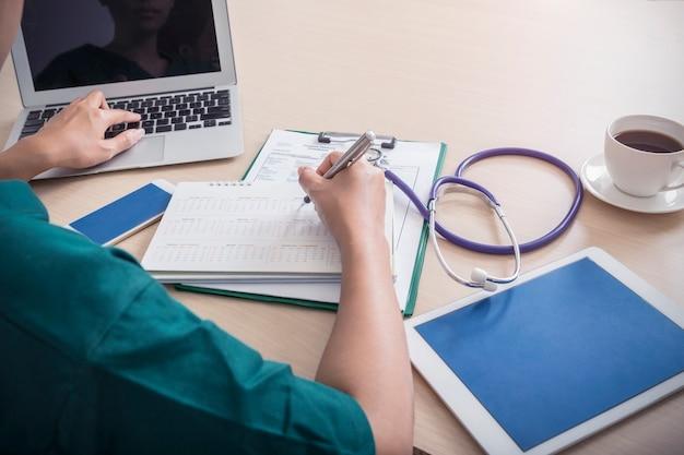 ヘルスケアと医療のコンセプト。医者は、ノートパソコン、モバイル、タブレット、聴診器、c