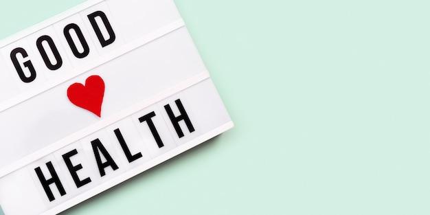 의료 및 의료 개념. 민트 컬러 배경에 단어 good health와 라이트 박스. 건강을 기원합니다. 평면도.