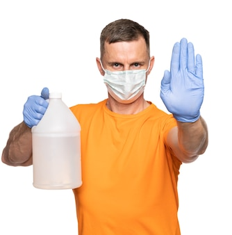 의료 및 의료 개념입니다. 의료용 얼굴 마스크와 장갑을 끼고 흰색 배경 위에 손을 닦기 위해 소독액 한 병을 들고 있는 남자