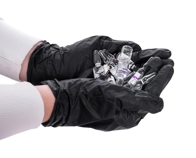 ヘルスケアと医療の概念。白い背景の上に彼女の手で多くの医療アンプルを保持している手袋の女医