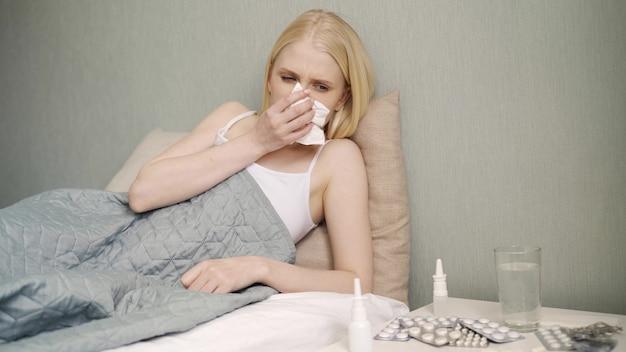 ヘルスケアと医療の概念。ソファで夜に自宅でくしゃみをする若い病気の女性