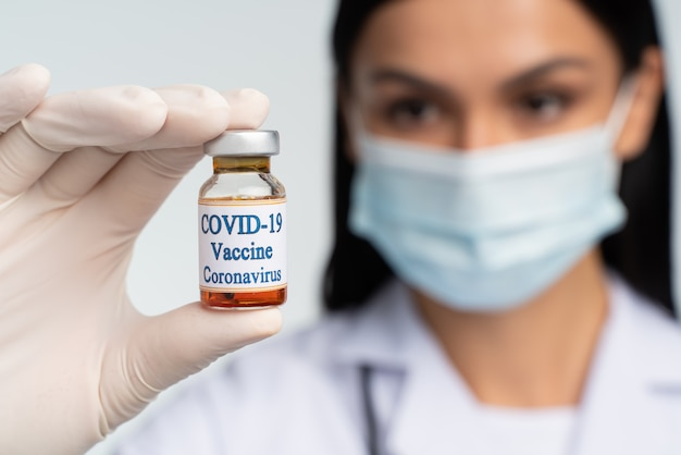 의료 및 의학 개념입니다. 청진기와 코비드 19 백신을 손에 들고 집중된 여의사의 모습. 약 병에 집중