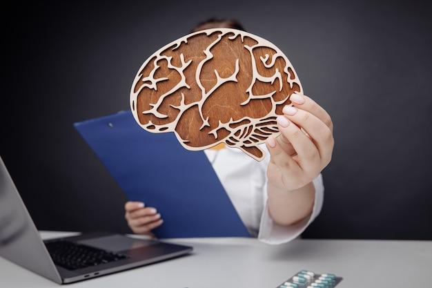 Концепция здравоохранения и лечения. доктор показывает крупный план деревянного мозга.