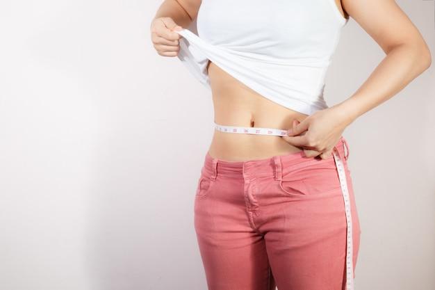 Концепция образа жизни диеты здравоохранения и женщины, чтобы уменьшить живот и сформировать здоровую мышцу живота.
