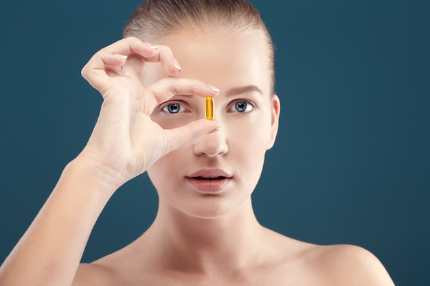 Healthcare and beauty concept - lovely woman with omega 3 vitami