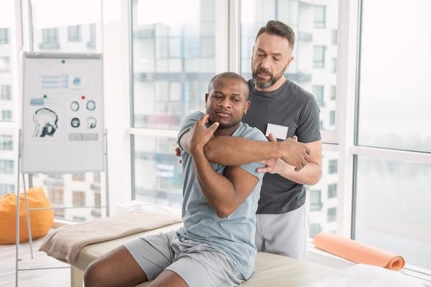 Медицинский центр. серьезный молодой человек двигает руками, пытаясь развить мышцы