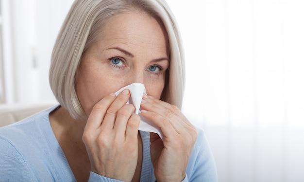 Здравоохранение, простуда, аллергия и больная женщина сморкается в бумажную салфетку.