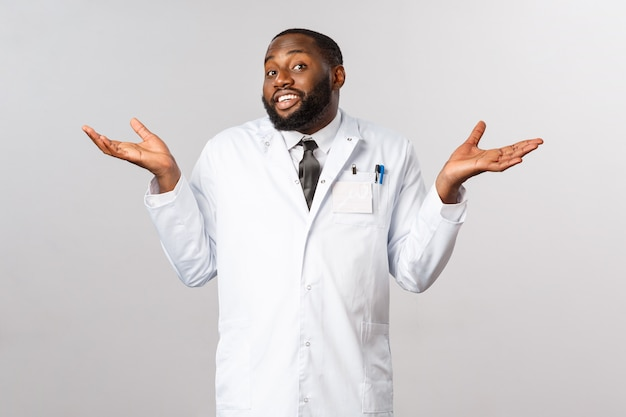 Healthcare concept. don't know cant help sorry. portrait of reluctant, unbothered handsome african-american doctor shrugging clueless, puzzled and have no idea