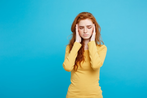 Healthcare concept - portrait of young beautiful ginger woman feeling sick and stressful. isolated on pastel blue background. copy space.