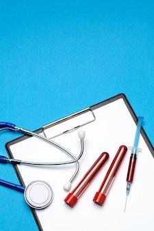 ヘルスケアの概念-聴診器、血液検査管、注射器、空白のシート付きクリップボード。