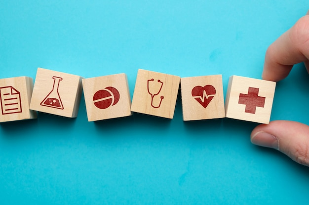 Healthcare concept with icons on wooden blocks.
