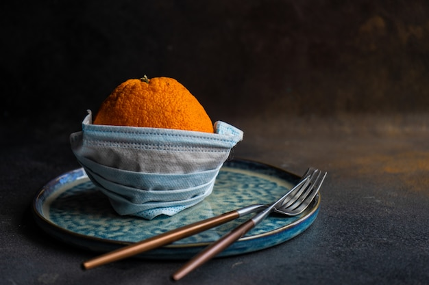 Healthcare concept with minimalistic table setting with orange fruit in face mask
