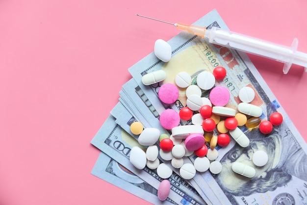 Концепция стоимости здравоохранения с долларом сша, таблеткой и шприцем на розовом фоне