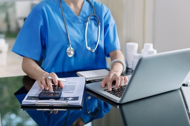 医療費と医療費の概念。スマートドクターの手は、朝の光の中で病院で医療費のために計算機とスマートフォン、タブレットを使用しました