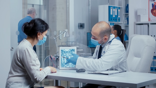 Healthcare diagnosis during covid-19 for woman patient who looks at x ray on a digital tablet through a plexiglass wall. medical consultation in protective equipment concept shot of sars-cov-2 global