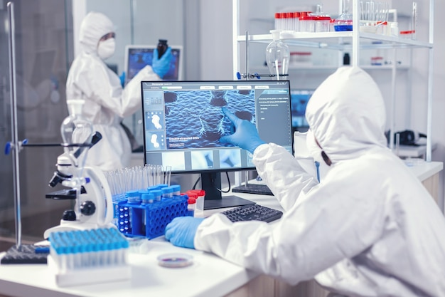 Healthcare doctors investigating evolution of coronavirus working on computer dressed in coverall