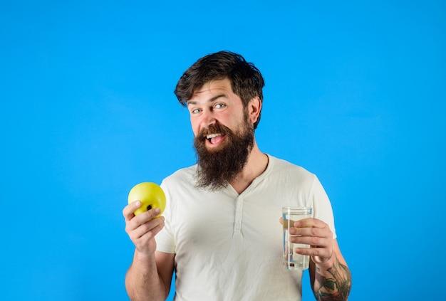 흰색 티셔츠를 입은 건강 관리 남자는 물을 들고 사과 남자는 물 한 잔과 잘 생긴 사과를 들고 있습니다.