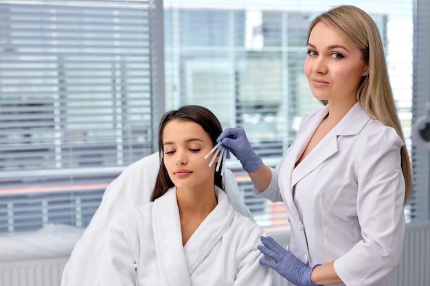 Концепция здравоохранения, медицины и хирургии. косметолог или врач с пациентом, готовящимся сделать инъекцию, подтяжку ниток, нить pdo. эстетическая красота против старения, операция по подтяжке лица. копировать пространство