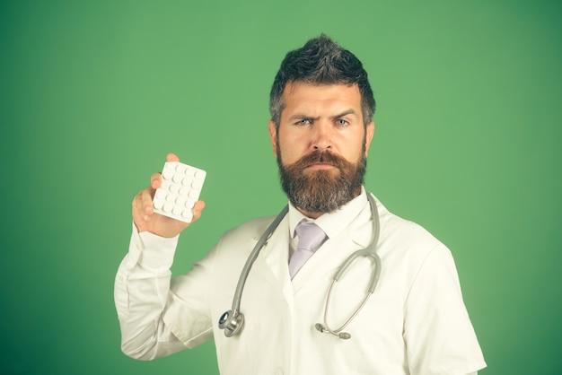 ヘルスケア、医療、病院、薬局のコンセプト-白衣を着たひげを生やした医師または薬剤師が、クリニックで聴診器を首に付けて丸薬を見せています。
