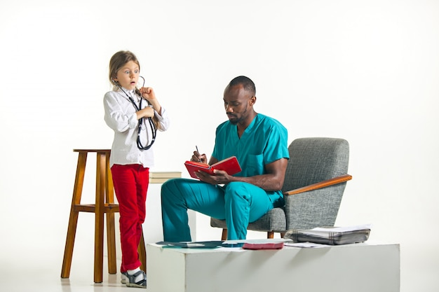 Healthcare and medical concept - doctor and girl with stethoscope in hospital