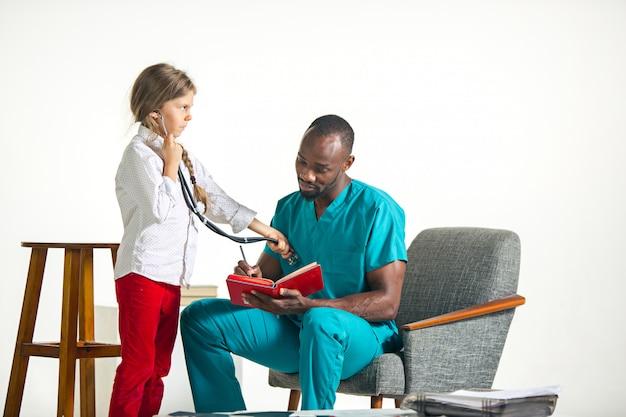 Sanità e concetto medico - medico e ragazza con lo stetoscopio in ospedale