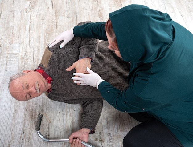 Healthcare and medical concept. woman giving first aid to an elderly man