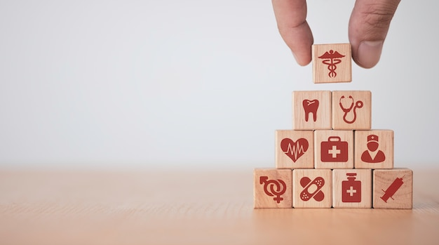 Healthcare medical and hospital concept, hand putting and stacking wooden block cubes which print screen healthcare icons on table with copy space.