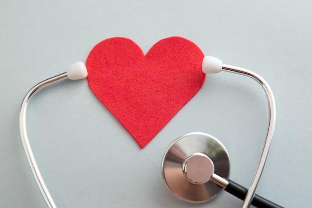 의료 의료 보험 사업 및 의사와 여자의 손 지원에 붉은 마음과 붕대 반창고와 세계 심장 건강의 날 개념