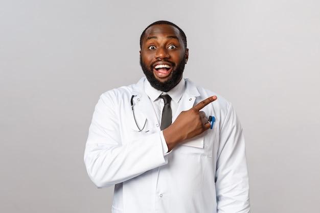 医療、医学、流行の概念。陽気な幸せ、笑顔のアフリカ系アメリカ人の医師が新しいクライアントをクリニックに招待し、ニヤリとカメラを熱狂的に見て、指を右に向ける
