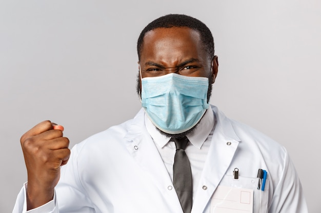 医療、医学、病院の治療コンセプト。アフリカ系アメリカ人の医師が勝利を収めて歓喜するクローズアップの肖像画がついに病気と戦った