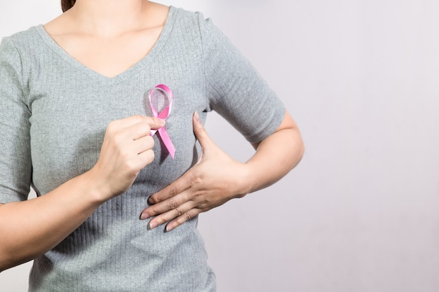 Healthcare, medicine and cancer awareness , woman with pink breast cancer awareness ribbon. copyspace