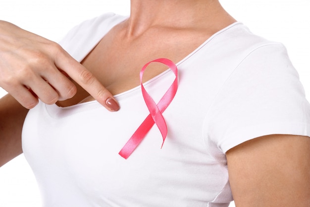 Healthcare and medicine concept - woman in white t-shirt with pink breast cancer awareness ribbon.