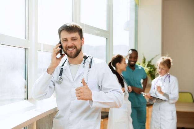 ヘルスケアの人々のグループ電話ポーズでプロの白人男性医師