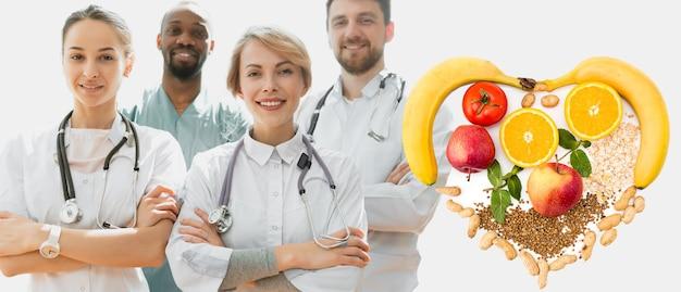 ヘルスケアの人々のグループは健康的な栄養をお勧めします。病院のオフィスや診療所でポーズをとるプロの笑顔の医師。医療技術研究所と医師スタッフのサービスコンセプト。