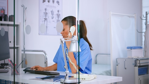 Healthcare physician answering phone calls from patient in hospital checking appointment. medical receptionist in medicine uniform, doctor nurse assistant helping with telehealth communication