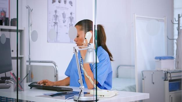 病院の患者からの電話に応答する医療医師が予約を確認します。医療ユニフォームの医療受付係、遠隔医療コミュニケーションを支援する医師看護助手