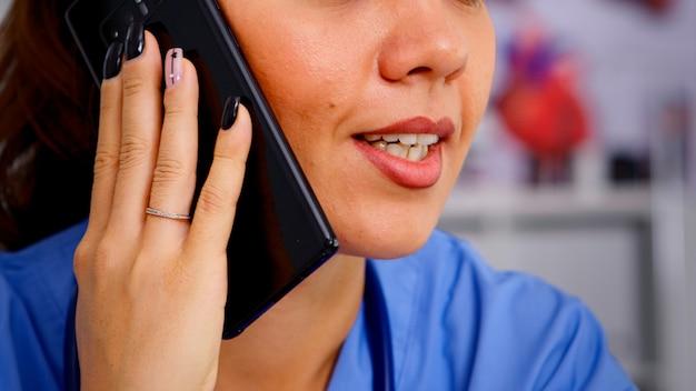 医療ユニフォームを着た病院で電話を使用して遠隔地の患者に相談する医療医師。遠隔医療コミュニケーション、診断で患者を支援する医師助手のクローズアップ