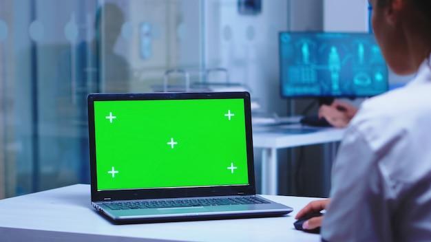 病室で緑色の画面でラップトップを使用している医療従事者。診療所のキャビネットに入る医学看護師。